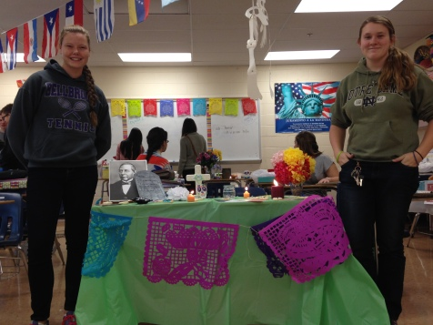 Seniors Megan Yates and Rachael Chandler display their altar to a Hispanic hero for Day of the Dead festivities.
